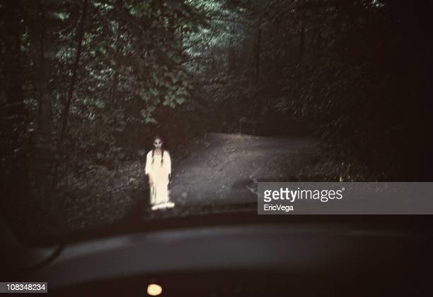 Spooky ghost in white standing in the middle of a dark road