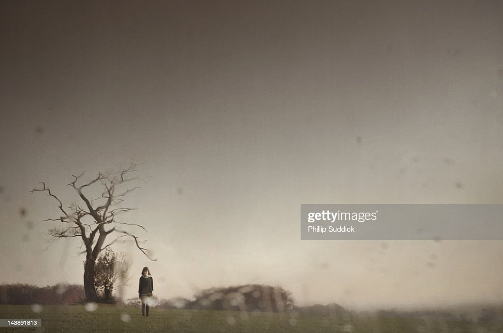 Spooky girl under petrified tree in stormy weather : Stock Photo