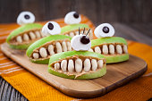 Spooky halloween edible apple monsters healthy natural dessert. Horror party decoration delicious snack. Homemade cute cyclop mouth with teeth and peanut butter on dark vintage wooden table background