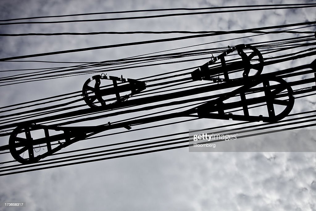 Spooled cables hang from an electricity pole in the Urca neighborhood of Rio de Janeiro, Brazil, on Monday, July 15, 2013. Energy developers in Brazil will bid for contracts to sell electricity Dec. 13 from plants due to go into operation in five years, including a 700-megawatt hydropower project in the Amazon. Photographer: Dado Galdieri/Bloomberg via Getty Images