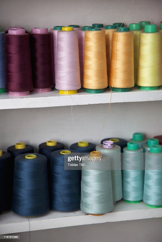Spools of colored cotton thread on shelves : Stock Photo