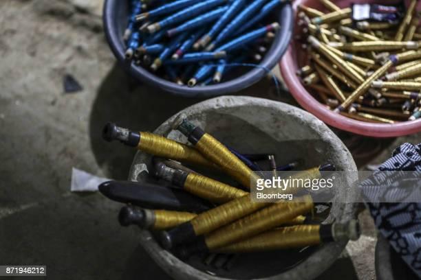 Spools of silk thread sit in bowls in a workshop at night in Varanasi Uttar Pradesh India on Friday Oct 27 2017 In Varanasi where the manufacture of...