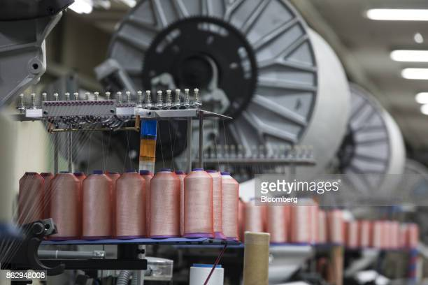 Spools of thread feed into a machine at a Hironen Textile Industry Co factory in Sakai Fukui Prefecture Japan on Tuesday Oct 10 2017 Fukui Prefecture...