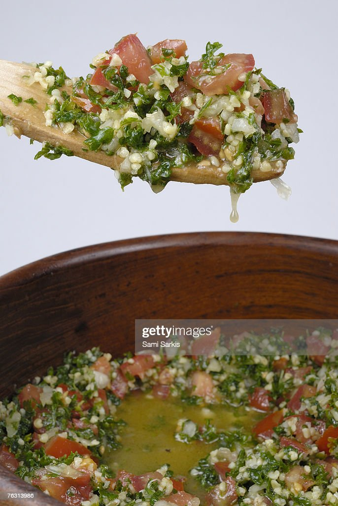 Spoon and bowl containing tabouli, close-up : Stock Photo