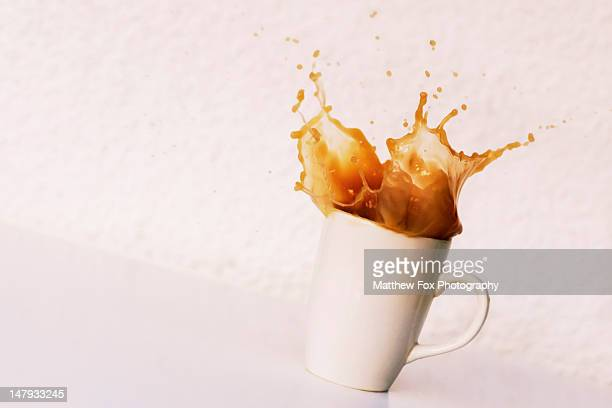 Spoon being dropped into mug of coffee.