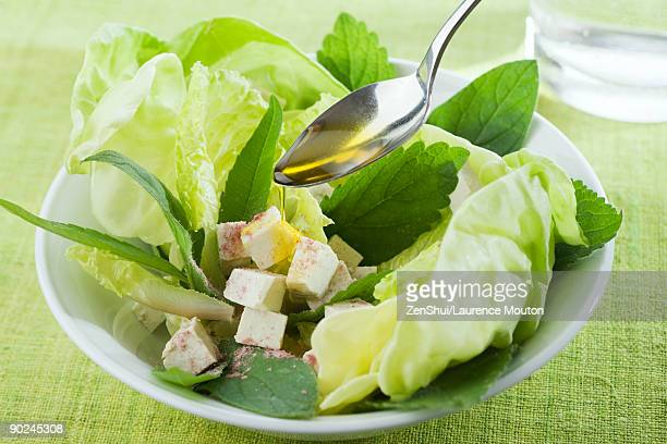 Spoon drizzling olive oil over salad of mixed greens and tofu cubes