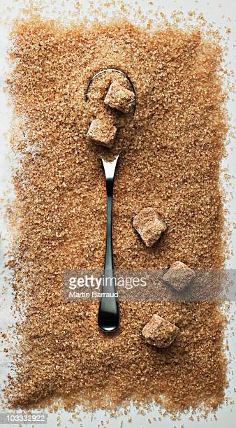 Spoon in heap of turbinado sugar