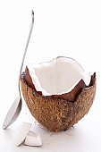 Spoon leaning on split coconut, close-up