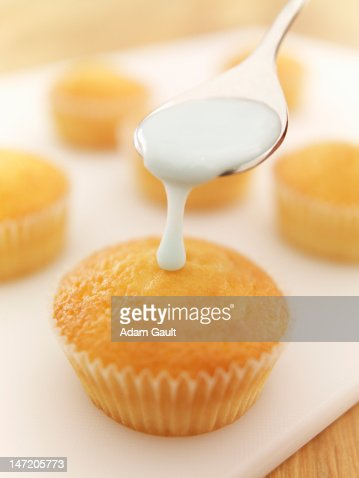 Spoon of icing dripping on cupcake : Stock Photo
