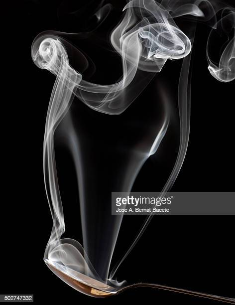 Spoon of metallic soup with a stela of smoke