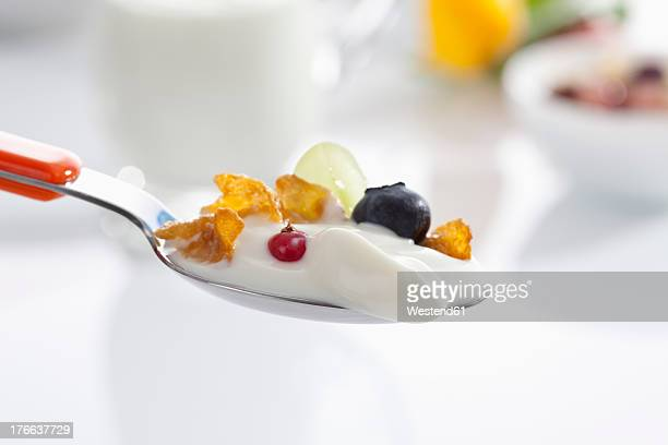 Spoon of yogurt with cornflakes and fruits against white background, close up