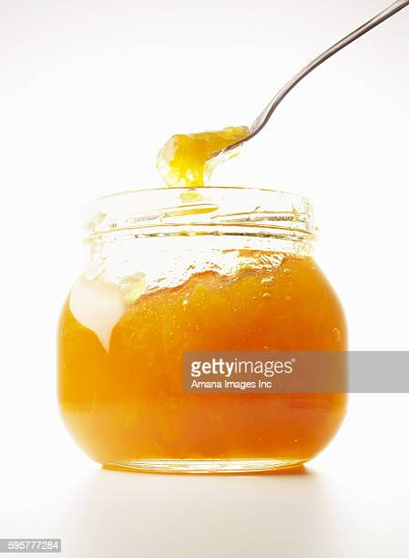 Spoon scooping marmalade in jar, close up, white background