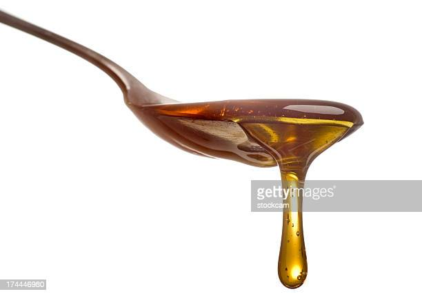 Spoon with dripping sirup or honey close-up