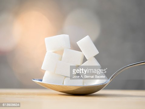 Spoon with nine lumps of sugar equivalent to the content in sugar of a refreshing drink