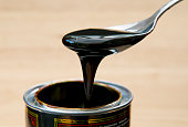 Spoonful of black treacle oozing off of spoon