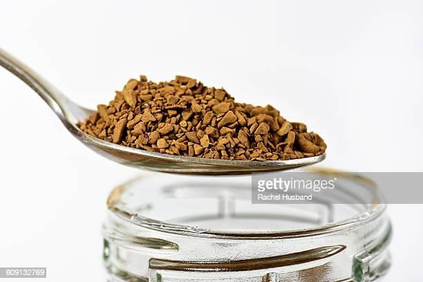 Spoonful of coffee granules over jar