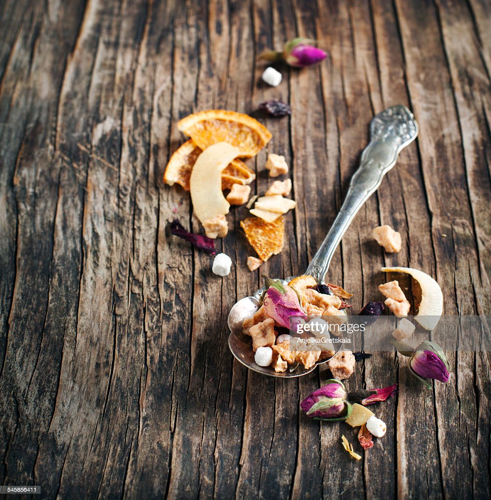 Spoonful of dried fruit tea on wooden table