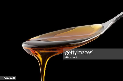 A spoonful of syrup drizzling down with a black background
