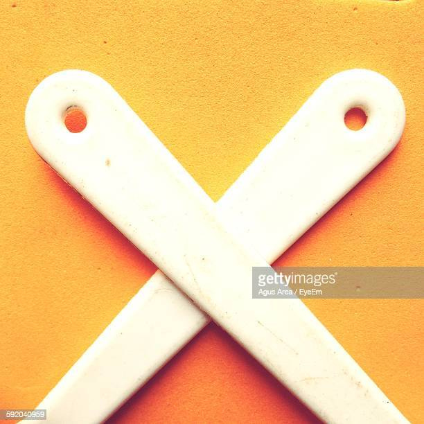 Spoons Forming Alphabet X Against Orange Wall