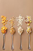 Spoons of various cereals view from above. Corn flakes, oat flakes, muesli, granola assortment. Top view