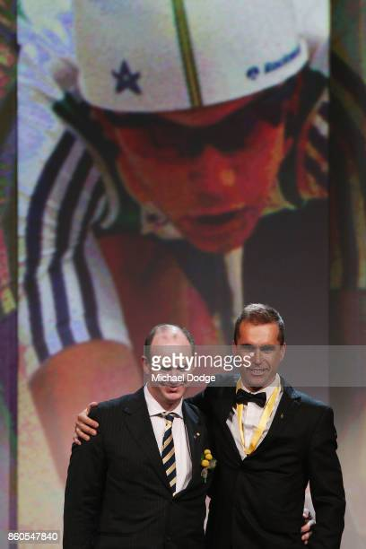 Sport Australia Hall of Fame Inductee and legend Cyclist Brad McGee poses with Ryan Bailey on stage at the Annual Induction and Awards Gala Dinner at...