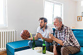 Senior Father and Adult Son Basketball Fans Watching Basketball Game on Tv in Their Livingroom. Elderly Man Watching Championship With Handsome Son With Basketball in Their Hands. Family, Sports and E