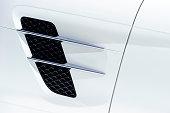 White sport car bodywork, metallic surface of racing vehicle, concept of aerodynamic high speed transport body, detail of door, wing and air intake