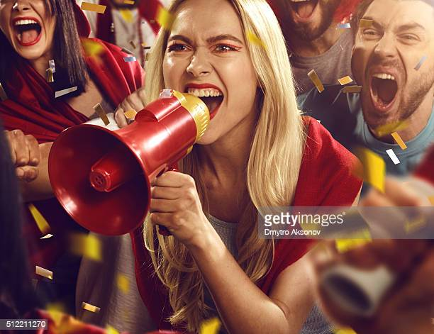 Sport fans: Girl is shouting in megaphone