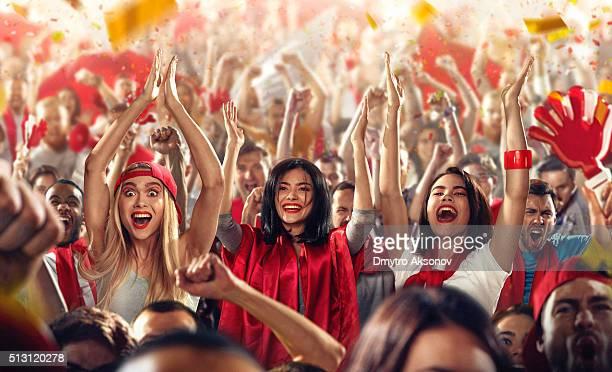 Sport fans: Three girls put hands in the air