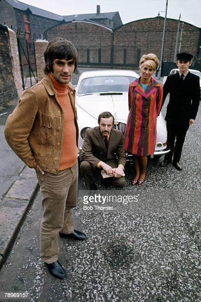 Sport Football 1960's Manchester United's George Best wearing suede cowboy style jacket stands with members of staff in front of one of his cars