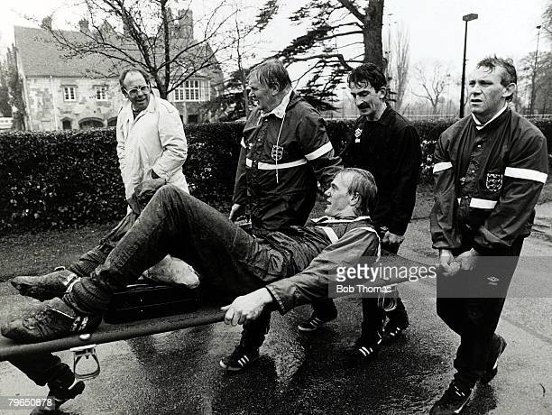 21st April 1986 England Training at Bisham Abbey England goalkeeper Gary Bailey is carried off after injuring his knee lr are journalist Bob Harris...