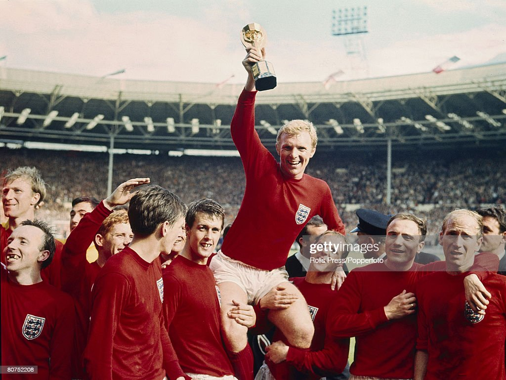 30th July 1966, 1966 World Cup Final at Wembley, England 4 v West Germany 2 a,e,t, England captain <a gi-track='captionPersonalityLinkClicked' href=/galleries/search?phrase=Bobby+Moore&family=editorial&specificpeople=206646 ng-click='$event.stopPropagation()'>Bobby Moore</a> holds aloft the World Cup (Jules Rimet trophy) as the team, from left to right: <a gi-track='captionPersonalityLinkClicked' href=/galleries/search?phrase=Jack+Charlton&family=editorial&specificpeople=453447 ng-click='$event.stopPropagation()'>Jack Charlton</a>, <a gi-track='captionPersonalityLinkClicked' href=/galleries/search?phrase=Nobby+Stiles&family=editorial&specificpeople=220308 ng-click='$event.stopPropagation()'>Nobby Stiles</a>, <a gi-track='captionPersonalityLinkClicked' href=/galleries/search?phrase=Gordon+Banks&family=editorial&specificpeople=215465 ng-click='$event.stopPropagation()'>Gordon Banks</a> (behind), <a gi-track='captionPersonalityLinkClicked' href=/galleries/search?phrase=Alan+Ball+-+World+Cup+Winner&family=editorial&specificpeople=213401 ng-click='$event.stopPropagation()'>Alan Ball</a>, <a gi-track='captionPersonalityLinkClicked' href=/galleries/search?phrase=Martin+Peters&family=editorial&specificpeople=643328 ng-click='$event.stopPropagation()'>Martin Peters</a>, <a gi-track='captionPersonalityLinkClicked' href=/galleries/search?phrase=Geoff+Hurst&family=editorial&specificpeople=206880 ng-click='$event.stopPropagation()'>Geoff Hurst</a>, <a gi-track='captionPersonalityLinkClicked' href=/galleries/search?phrase=Bobby+Moore&family=editorial&specificpeople=206646 ng-click='$event.stopPropagation()'>Bobby Moore</a>, <a gi-track='captionPersonalityLinkClicked' href=/galleries/search?phrase=Ray+Wilson&family=editorial&specificpeople=908340 ng-click='$event.stopPropagation()'>Ray Wilson</a>, <a gi-track='captionPersonalityLinkClicked' href=/galleries/search?phrase=George+Cohen&family=editorial&specificpeople=703599 ng-click='$event.stopPropagation()'>George Cohen</a> and <a gi-track='captionPersonalityLinkClicked' href=/galleries/search?phrase=Bobby+Charlton&family=editorial&specificpeople=204207 ng-click='$event.stopPropagation()'>Bobby Charlton</a>, gather round to celebrate.