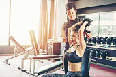 Sport girl doing weight exercises  working with heavy dumbbells  her personal trainer at Gym workout