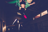 Photo of a young woman who is jumping thrilled on the trampoline, loving her daily exercise