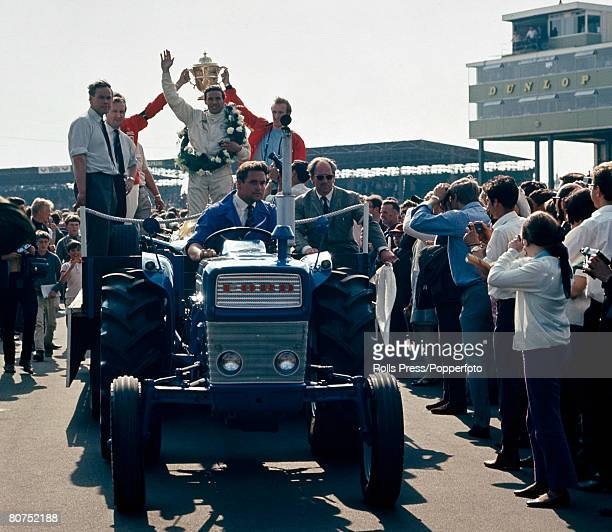 Sport Motor Racing Circa 1960's England Driver Jim Clark waves to the crowd while riding on the back of a tractor after winning the British Grand Prix