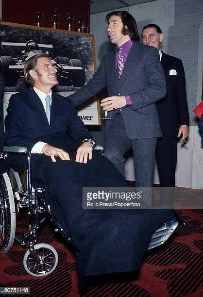 Sport Motor Racing London England November 1969 Formula One World Champion racing driver Jackie Stewart talks to Graham Hill who is sitting in a...