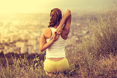 Young woman sits in yoga pose with city on background. Freedom concept. Calmness and relax, woman happiness. Toned image