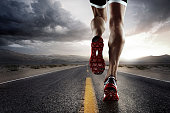 low angle view of male runners legs running down road wearing trainers