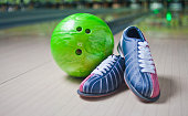 """Sport Shoes and green ball on floor in bowling club""""n"""