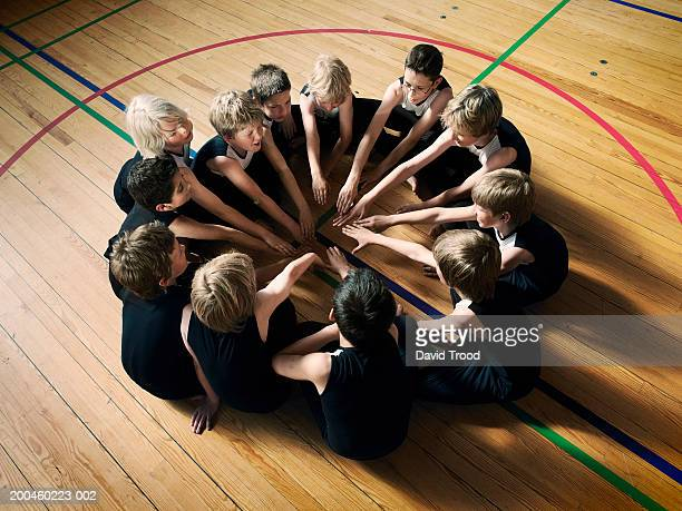 Sport team (7-9) sitting in circle in gym, overhead view