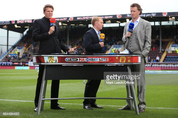 Sport television presenter Jake Humphrey stands behind the pitchside desk alongside pundits Paul Scholes and Steve McManaman prior to the Barclays...