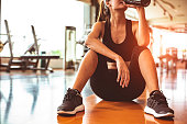 Sport woman relax resting after workout or exercise in fitness gym. Sitting and drinking protein shake or drinking water on floor. Strength training and Bodybuilder muscle theme. Warm and cool tone