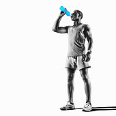 Young muscular build man drinking water of bottle after running, attractive athlete resting after workout outdoors, fitness and healthy lifestyle concept. Isolated on white