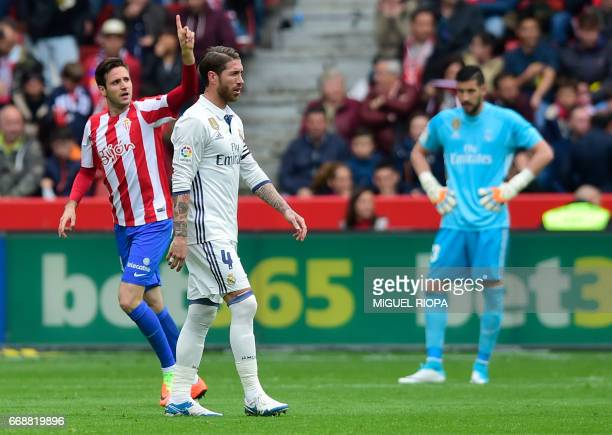 Sporting Gijon's Croatian forward Duje Cop celebrates after scoring a goal next to Real Madrid's defender Sergio Ramos during the Spanish league...