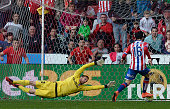 TOPSHOT Sporting Gijon's forward Carlos Castro kicks the ball next to Atletico Madrid's Slovenian goalkeeper Jan Oblak to score a goal during the...