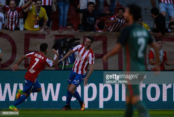 Sporting Gijon's forward Victor Rodriguez celebrates with teammate forward Burgui Franco after scoring a goal during the Spanish league football...