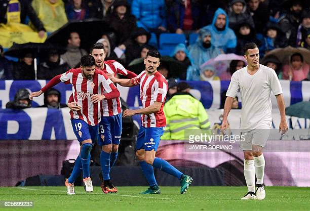 Sporting Gijon's midfielder Carlos Carmona celebrates a goal with teammates beside Real Madrid's midfielder Lucas Vazquez during the Spanish league...