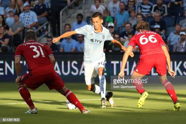 Sporting Kansas City forward Daniel Salloi winds up to score a goal between Chicago Fire midfielder Bastian Schweinsteiger and defender Joao Meira in...