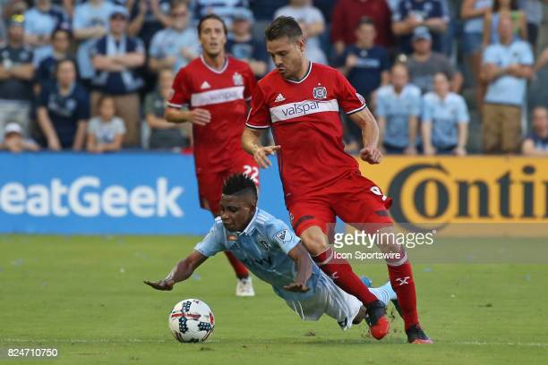 Sporting Kansas City forward Latif Blessing goes down fighting for the ball against Chicago Fire forward Luis Solignac in the first half of an MLS...