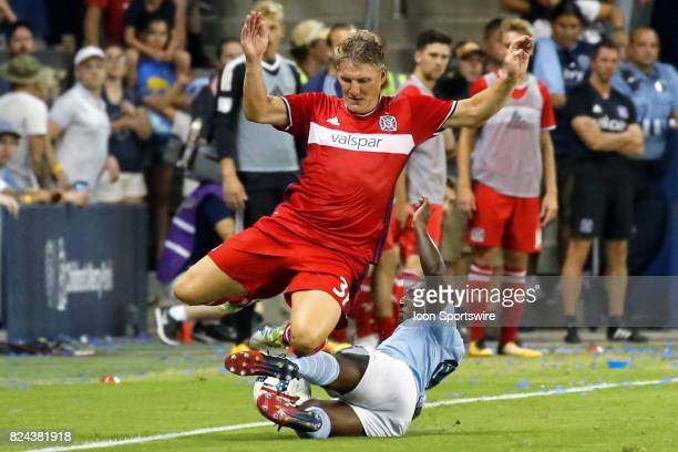Sporting Kansas City midfielder Jimmy Medranda makes a sliding tackle against Chicago Fire midfielder Bastian Schweinsteiger in the second half of an...